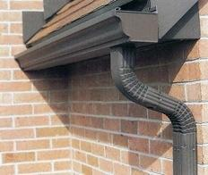 a downspout in San Jose at the end of a Tudor Style door arch