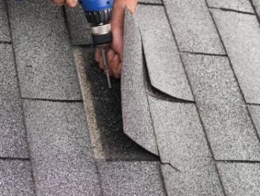 a Campbell roofer installs a replacement shingle with a power driver