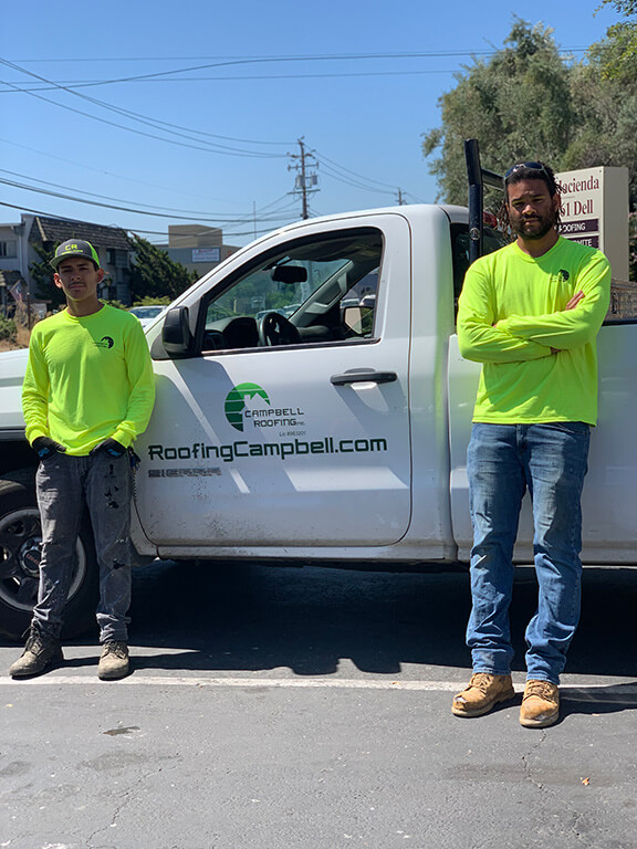 Roofers pose with truck
